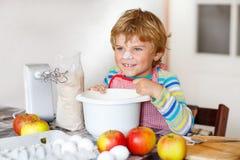 Funny blond kid boy baking apple cake indoors Royalty Free Stock Photo