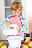Funny blond kid boy baking apple cake indoors Stock Images