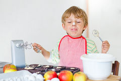 Funny blond kid boy baking apple cake indoors Royalty Free Stock Photos