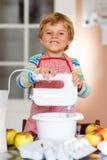 Funny blond kid boy baking apple cake indoors Royalty Free Stock Photography