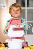 Funny blond kid boy baking apple cake indoors Royalty Free Stock Image