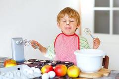 Funny blond kid boy baking apple cake indoors Stock Image