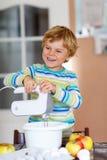 Funny blond kid boy baking apple cake indoors Stock Images