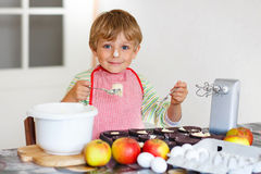 Funny blond kid boy baking apple cake indoors. Cute funny blond preschool kid boy baking apple cake and muffins in domestic kitchen. Happy child having fun with Stock Photography