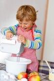 Funny blond kid boy baking apple cake indoors Stock Photo