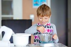 Funny blond kid boy baking cake indoors Stock Photo