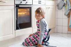Funny blond kid boy baking muffins indoors Stock Images