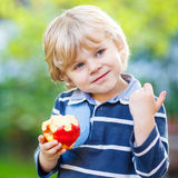 Funny blond kid boy eating healthy apple. Beautiful little kid boy with apple on his first day to elementary school or nursery. Outdoors.  Back to school, kids Royalty Free Stock Photo