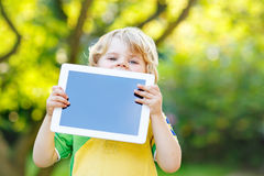 Funny blond kid boy holding tablet pc, Stock Photography