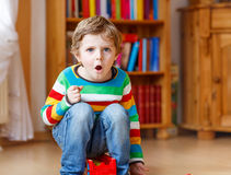 Funny blond kid boy shouting and playing, indoors Stock Photo