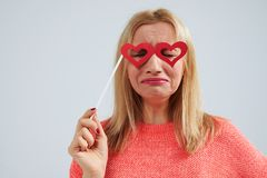 Funny blond in paper heart shaped glasses crying. Studio shot Stock Photography