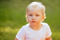 Funny blond toddler boy in summer garden stock photography