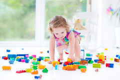 Funny blond toddler girl sitting on floor in mess stock photography
