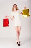 Funny blond woman with shopping bags Royalty Free Stock Images