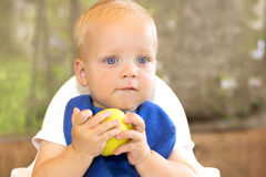 Funny blonde blue-eyed toddler in a blue bip eating an apple. Outdoor shot. Blurred background royalty free stock images