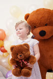 Funny blonde girl posing with teddy bears Stock Photos