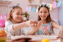 Funny blonde girl showing her result to sister. Playful mood. Beautiful girls expressing positivity while spending time together royalty free stock photo
