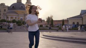 Funny blonde having fun on the street, a girl dancing and laughing with a phone in her hands. 4K. Funny blonde having fun on the street, a girl dancing and stock video footage