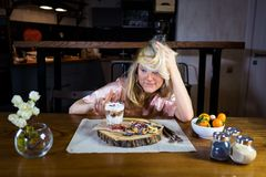 Funny blonde sits at the table with food against modern kitchen Royalty Free Stock Photos