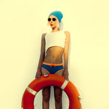 Funny blonde on wall background with lifebuoy Stock Photography