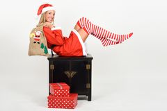 Funny blonde woman in Santa Claus clothes on white background. Beautiful happy blonde woman in Santa Claus clothes and striped socks moving her legs. Young funny Stock Images