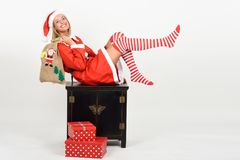 Funny blonde woman in Santa Claus clothes on white background. Beautiful happy blonde woman in Santa Claus clothes and striped socks moving her legs. Young funny Royalty Free Stock Image