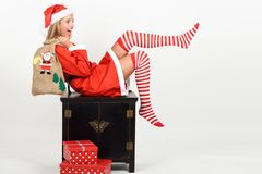 Funny blonde woman in Santa Claus clothes on white background. Beautiful happy blonde woman in Santa Claus clothes and striped socks moving her legs. Young funny Royalty Free Stock Images