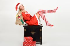 Funny blonde woman in Santa Claus clothes on white background. Beautiful happy blonde woman in Santa Claus clothes and striped socks moving her legs. Young funny Stock Image