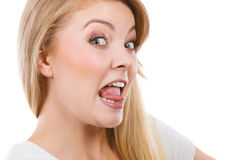 Funny blonde woman sitcking tongue out stock photo