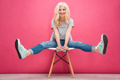 Funny blonde woman sitting on the chair Stock Photography