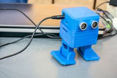 Funny blue robot printed on a 3D printer. Toy cute automatic rob stock photo