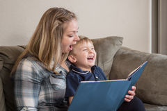 A Funny Book. A young boy laughs as his mother reads him a story with great expression Royalty Free Stock Image