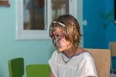Funny boring, hostile unhappy little girl sitting with painted face at kids club Royalty Free Stock Images