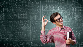 Funny botanist. Young funny man in glasses against chalkboard with sketches Royalty Free Stock Photos