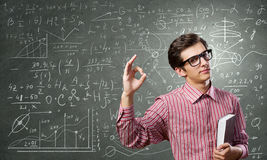 Funny botanist. Young funny man in glasses against chalkboard with sketches Stock Images
