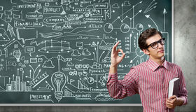 Funny botanist. Young funny man in glasses against chalkboard with sketches Stock Photo