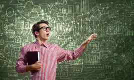 Funny botanist. Young funny man in glasses against chalkboard with sketches Stock Photography