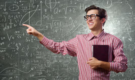 Funny botanist. Young funny man in glasses against chalkboard with sketches Royalty Free Stock Photo