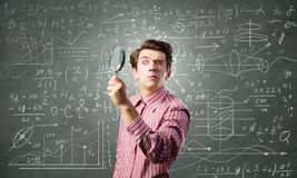 Funny botanist. Young man scientist looking in magnifying glass Stock Image