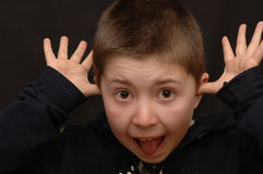 Funny Boy. Humorous shot of a 9 year old boy with his tongue sticking out, and his thumbs in his ears. Isolated on dark background royalty free stock photo