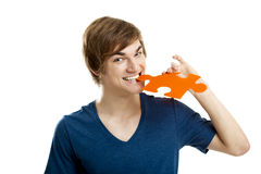 Funny boy. Young man holding and biting a puzzle piece, isolated on white background Stock Images