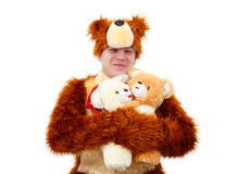 Funny boy in bear suit embrace a couple of toy bears Royalty Free Stock Photo