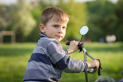 Funny boy with bicycle having fun in summer park Stock Photo