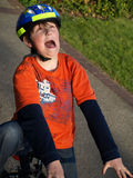 Funny boy on the bike with helmet. Boy on the bike with very funny face Royalty Free Stock Photo