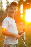 Funny boy with bike at the summer park in beam of sunset Stock Photo