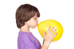 Funny boy blowing up a yellow balloon royalty free stock photos