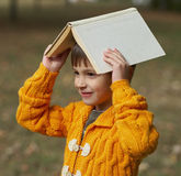 Funny boy with book on his head Royalty Free Stock Photos