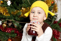 Funny boy with can of jam. Under the christmas tree Stock Images