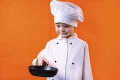 Funny boy chef in uniform holding an empty frying pan. On a bright orange background Royalty Free Stock Photos