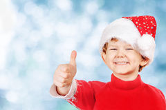 Funny boy in a Christmas hat on blue snow bokeh background. Laughing funny child in a Christmas hat, showing thumbs up stock images